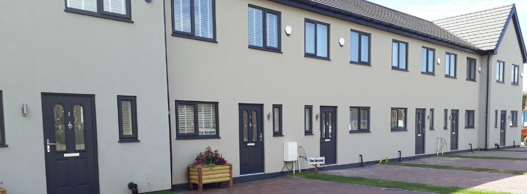 Modern SIPs terraced affordable homes with grey features and monoblock drive